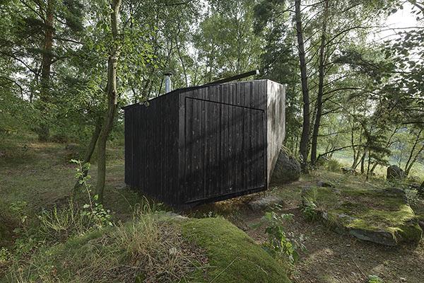Lesní útulna, černý objekt posazený na kameni