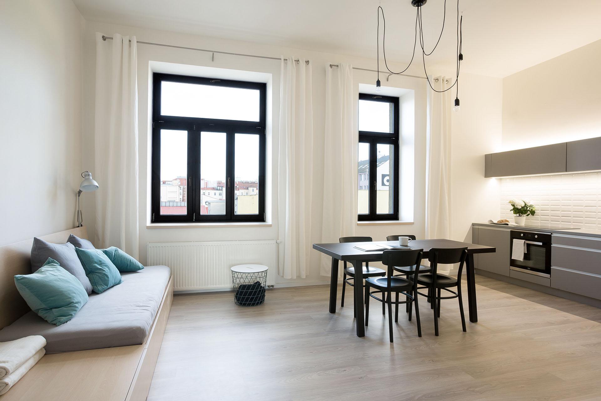 Společenský prostor bytu s jídelním stolem a kuchyňskou linkou