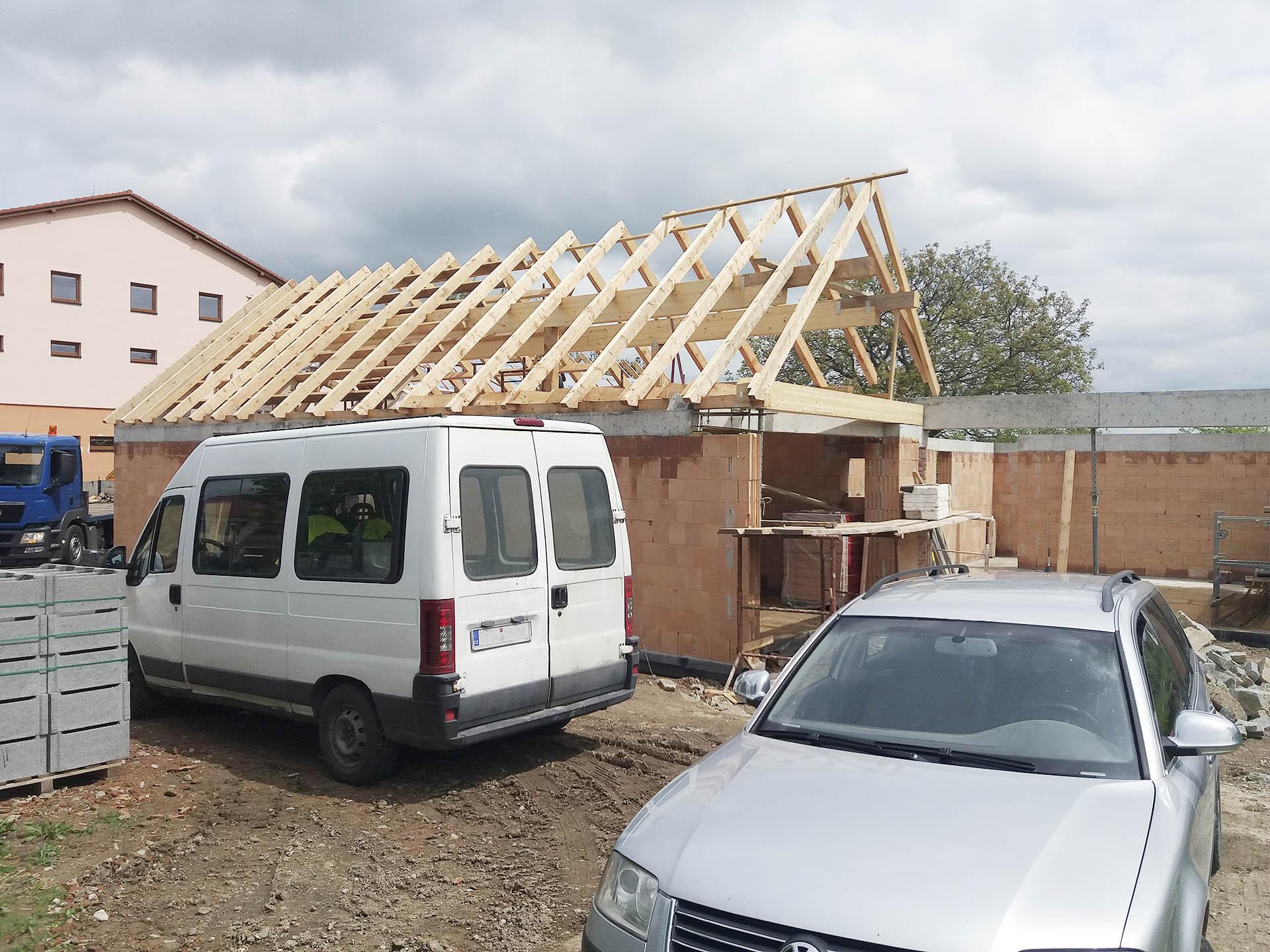 Stavba konstrukce krovu s lepenými vazníky při pohledu z ulice