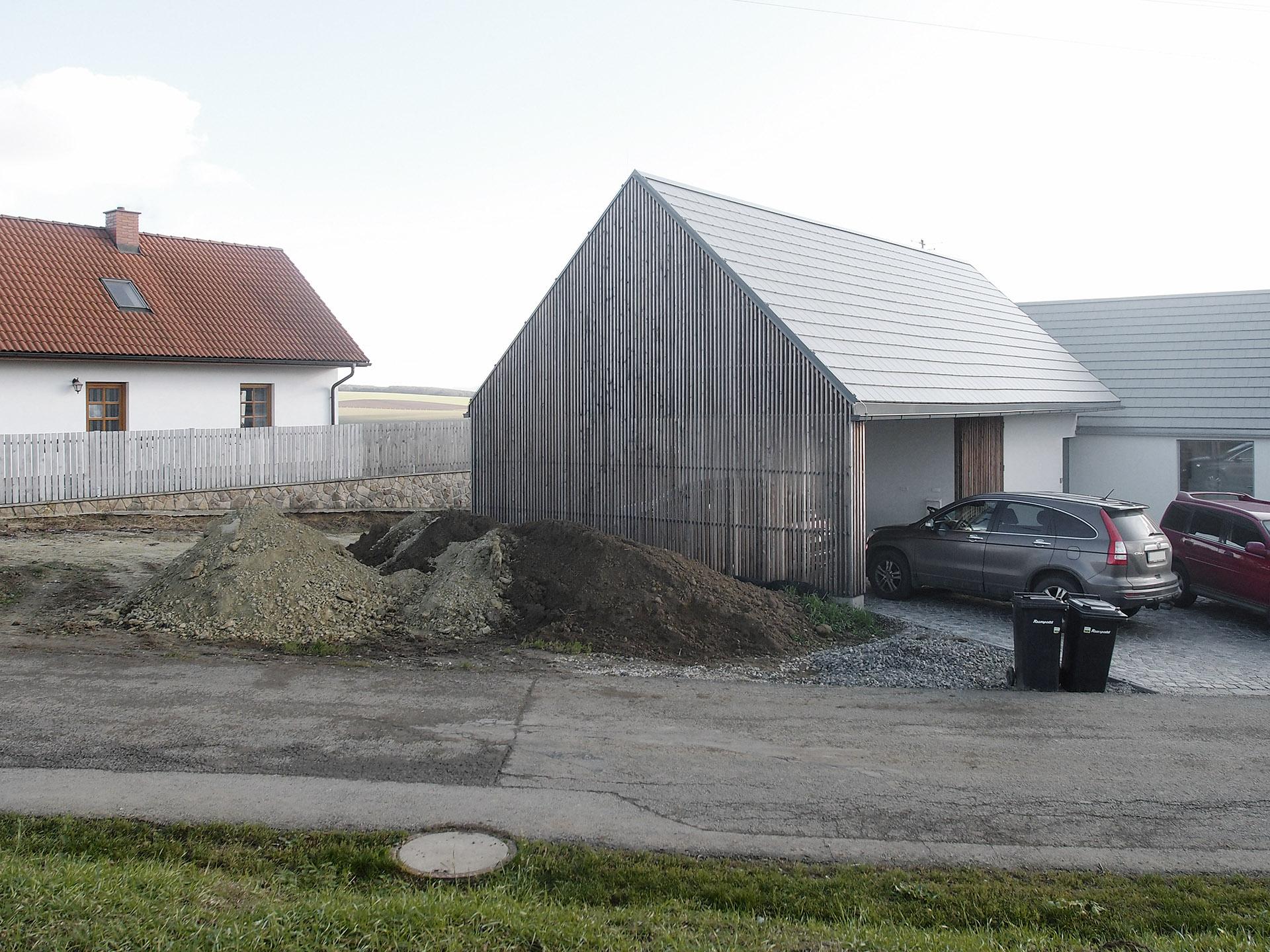 Kryté stání u domu, dřevěný štít do ulice
